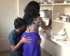 Indian mother and son business in kitchen